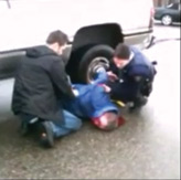 Photo courtesy of YouTube.  RCMP officers watch over 51-year-old, Buddy Tavaras after he was kicked in the face.