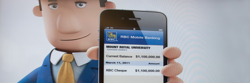 Photo by Bryan Weismiller.  TV screens in the Bissett School of Business displayed this image, showcasing the transfer of the donation to Mount Royal via a Blackberry application.