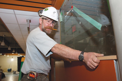 Photo by Bryan Weismiller.  Mike Birse, of Mantei Construction, installs a piece of slotwall in a section of the EC building expansion. The expansion will create more space for growing credit and credit-free departments on campus.