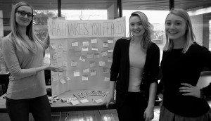 "Students Andrea Janish, Alex Blackwell and Bridgette Slater stand beside their creation: a poster asking MRU, ""What makes you feel fearless?"" For answering, students receive a box of matches held together with a bobby pin 