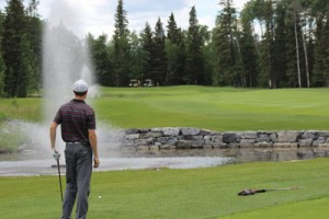Local golfer Ryan Hounjet stares down his second shot at the par 5 18th hole at Priddis Greens Golf and Country Club | Photo by Brendan Stasiewich